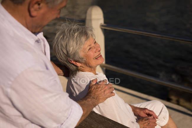 Senior couple sitting on bench near sea side at promenade — Stock Photo
