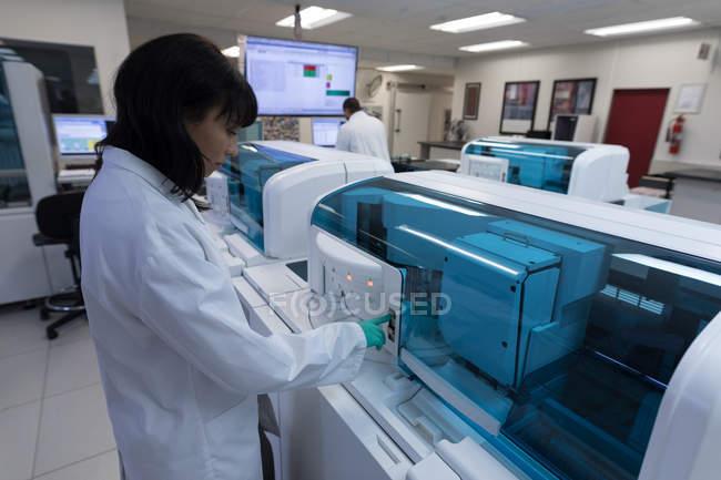 Aufmerksame Laborantin mit Maschine in Blutbank — Stockfoto