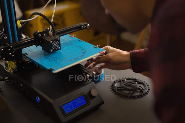 Mecánico atento trabajando en la máquina de troquel en la mesa - foto de stock