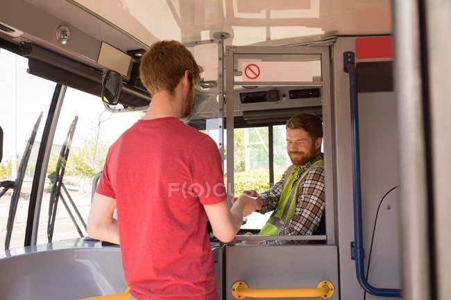 Мужчины пригородных принимает билет у водителя в современный автобус — стоковое фото