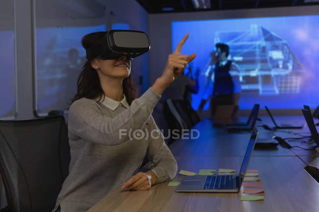 Бізнес-леді за допомогою віртуальної реальності гарнітуру в конференц-залі, в офісі — стокове фото