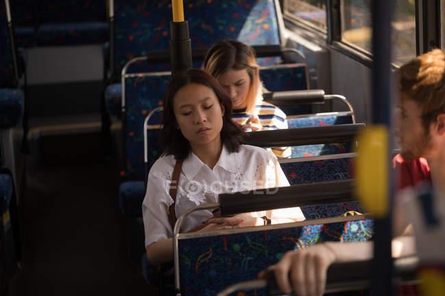 Femmina dell'abbonato utilizzando il telefono cellulare durante un viaggio in autobus moderno — Foto stock