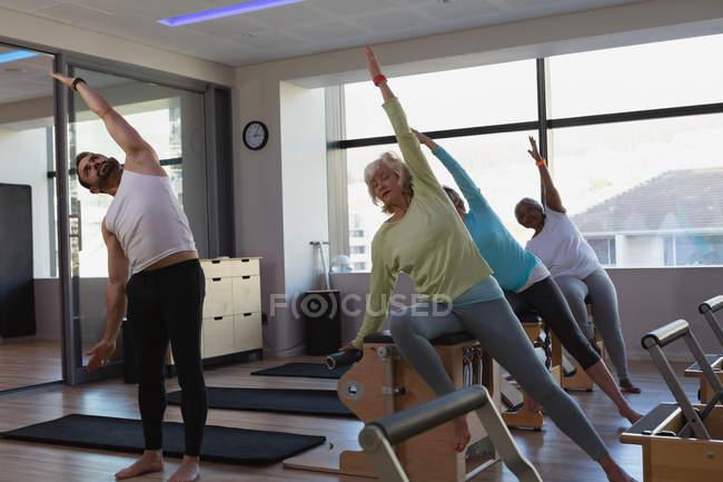 Тренер инструктирует группу пожилых женщин по йоге в центре йоги — стоковое фото