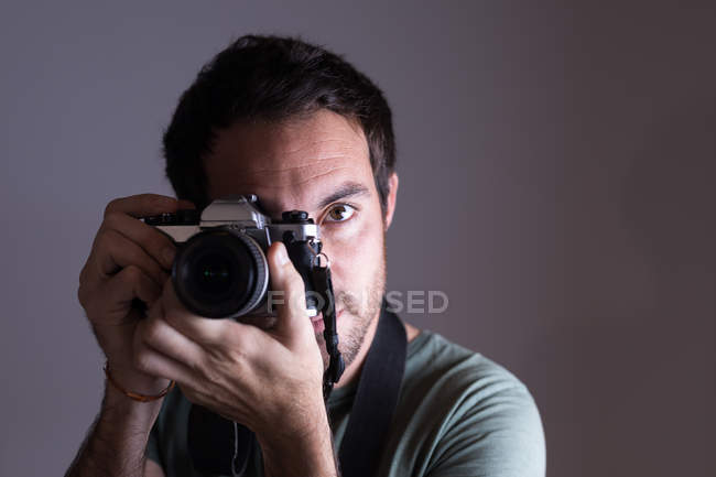 Male photographer clicking photos with camera in photo studio — Stock Photo