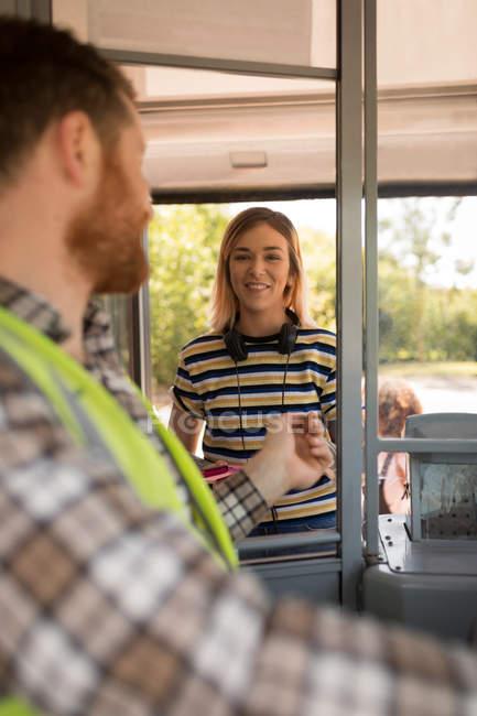 Женщины пригородных принимает билет у водителя в современный автобус — стоковое фото
