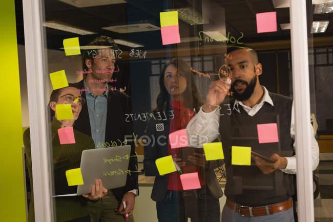 Бизнесмен пишет на стеклянной доске в офисе — стоковое фото