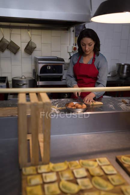 Mujer en el delantal usando laptop en la cocina - foto de stock