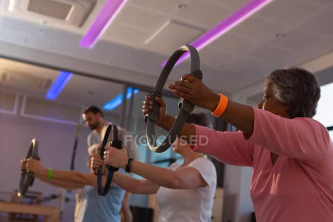Donne anziane che praticano yoga con ruota yoga nel centro yoga — Foto stock