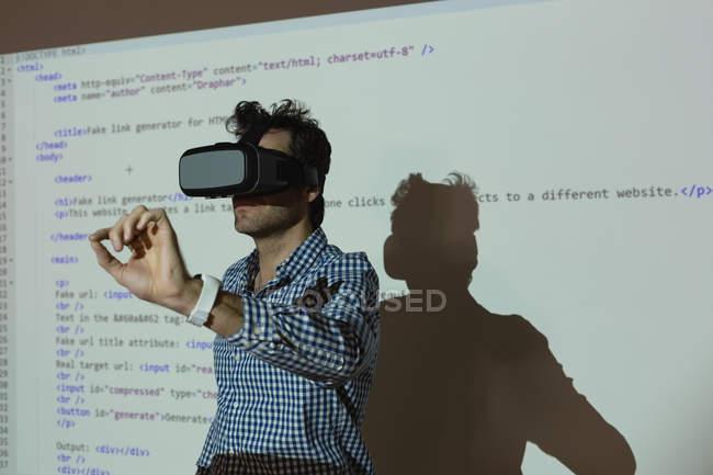 Hombre de negocios con auriculares de realidad virtual en la sala de conferencias en la oficina - foto de stock