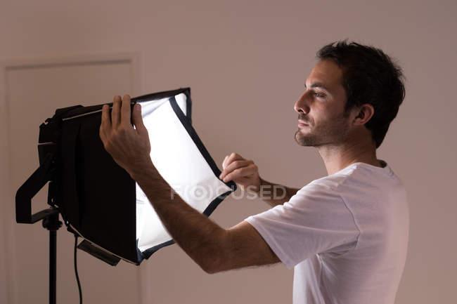Männlichen Fotografen anpassen Stroboskoplicht im Fotostudio — Stockfoto