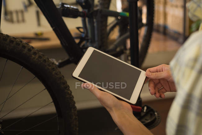 Close-up of man using digital tablet in workshop — Stock Photo