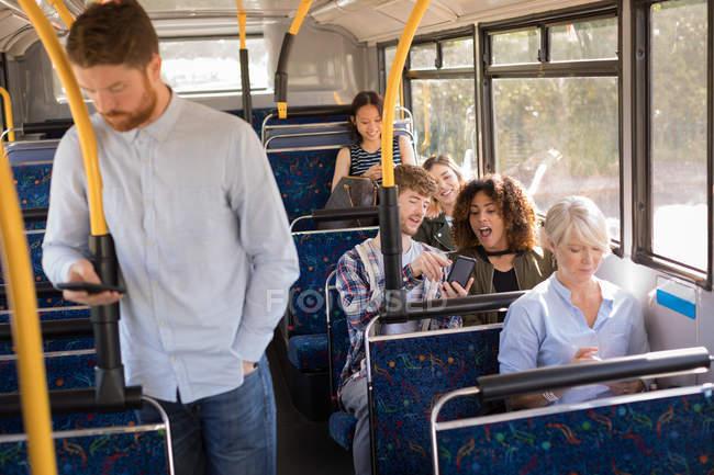 Smart männliche Pendler mit Handy während der Fahrt in modernen Bussen — Stockfoto