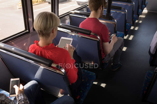 Overhead of female commuter using digital tablet while travelling in modern bus — Stock Photo