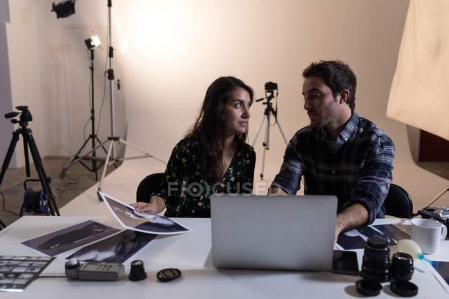 Fotógrafo masculino e feminino interagindo uns com os outros no estúdio de fotografia — Fotografia de Stock