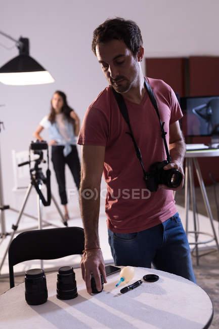 Fotógrafo masculino mudando de lente da câmera no estúdio de fotos — Fotografia de Stock