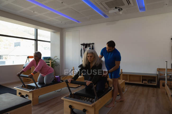 Trainer assistere le donne anziane durante l'esecuzione di yoga nel centro yoga — Foto stock