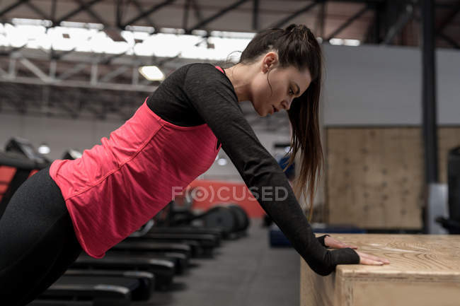 Fit woman doing push up exercise in fitness studio — Stock Photo