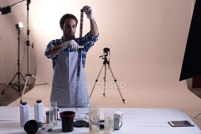 Fotógrafo masculino checando filmstrip câmera no estúdio de fotos — Fotografia de Stock