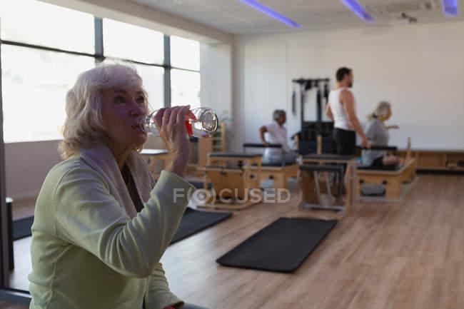 Ältere Frau Trinkwasser im Yogazentrum — Stockfoto