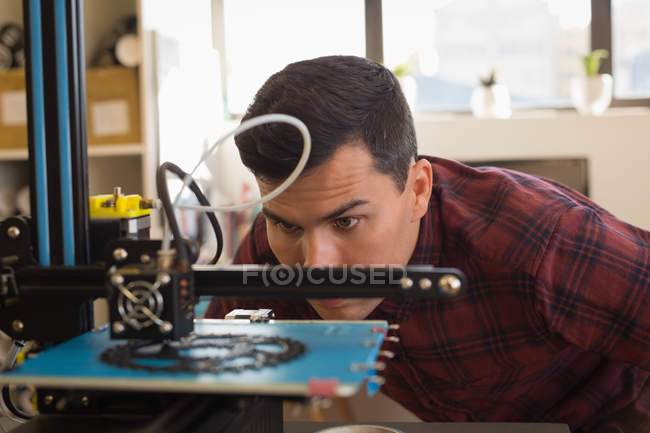Attentive mechanic examining die machine in workshop — Stock Photo