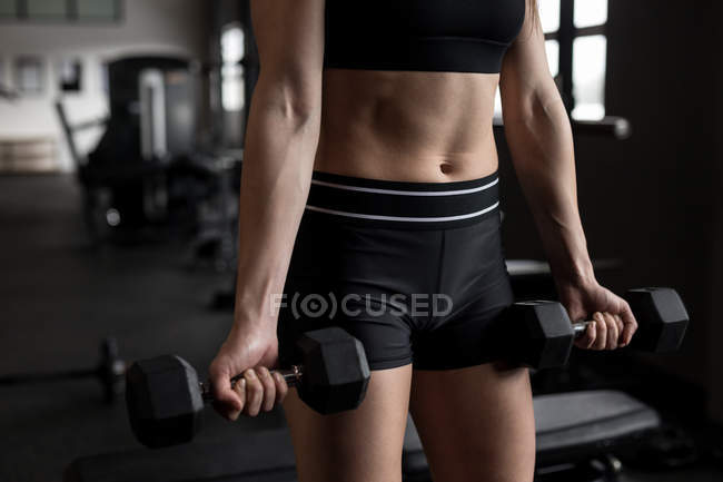 Mid section of women exercising with dumbbell in fitness studio — Stock Photo