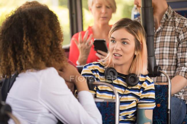 Freundinnen Interaktion während der Fahrt im modernen bus — Stockfoto