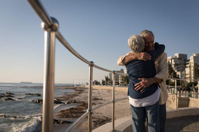 Senior couple embracing each other near sea side at promenade on a sunny day — Stock Photo