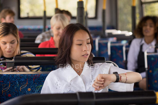 Female commuter checking time while travelling in modern bus — Stock Photo