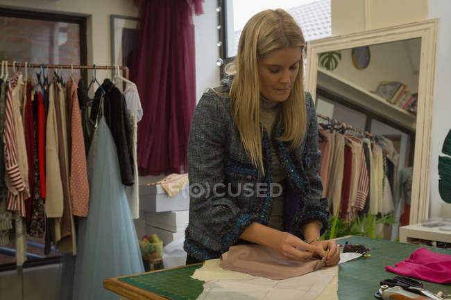 Beautiful fashion designer pinning on fabric in fashion studio — Stock Photo