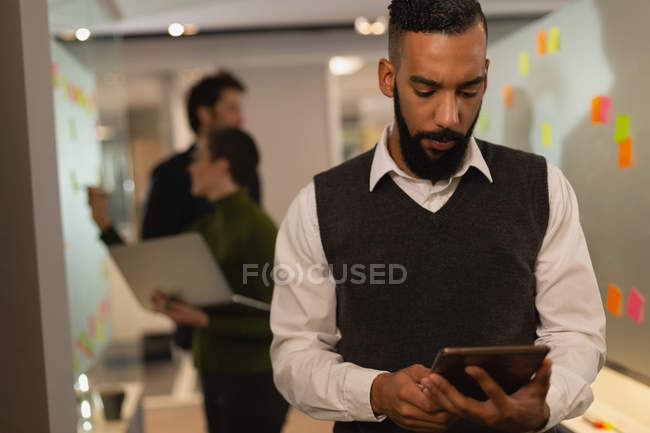 Attentive businessman using digital tablet at office — Stock Photo