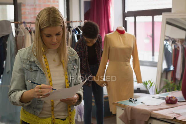 Beautiful fashion designer checking sketch in fashion studio — Stock Photo