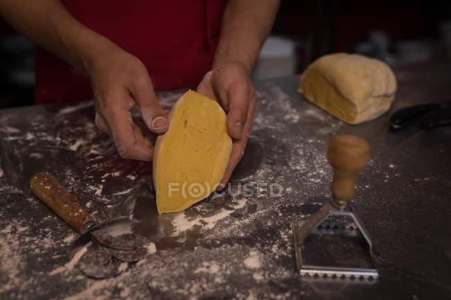 Panettiere mostrando taglio pezzo di pasta in panetteria — Foto stock