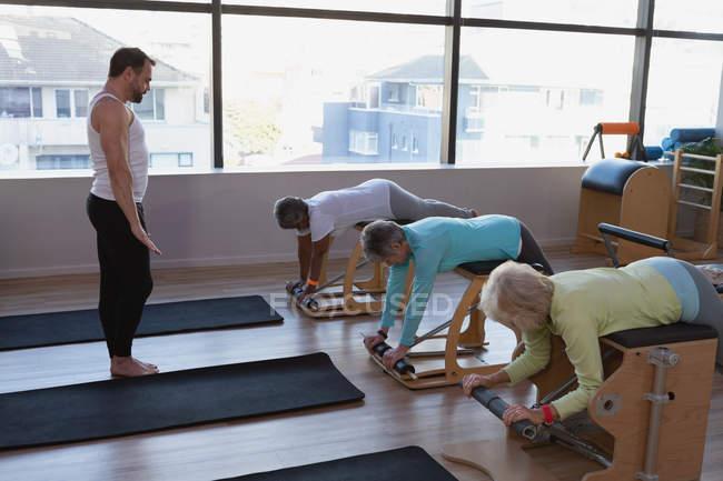 Тренер, инструктируя группы старших женщин в центр йоги — стоковое фото