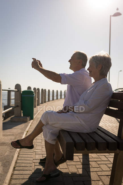 Happy senior couple taking pictures from mobile at promenade — Stock Photo
