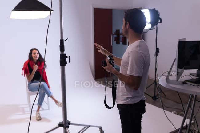 Fotografo maschile e modella femminile che interagiscono tra loro in studio fotografico — Foto stock
