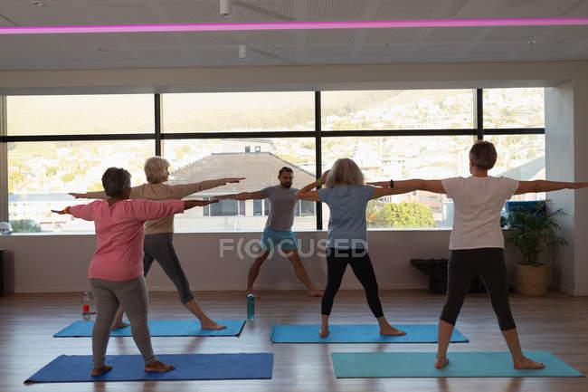 Trainer assistere le donne anziane nello svolgimento di yoga presso il centro yoga — Foto stock