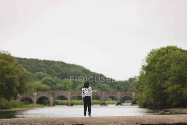 Rückansicht eines Mädchens, das auf einer Mauer in der Nähe des Flusses steht — Stockfoto