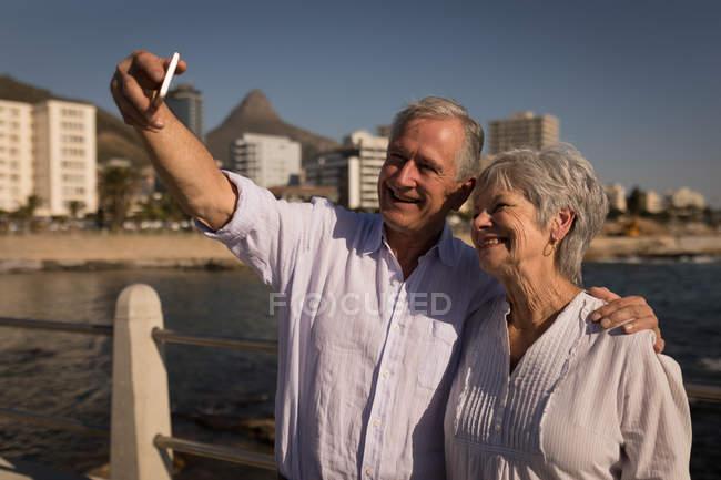 Smiling senior couple taking selfies at promenade — Stock Photo