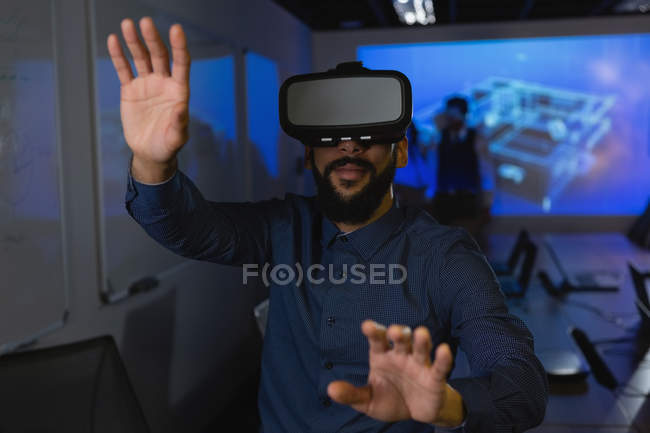 Businessman using virtual reality headset in conference room at office — Stock Photo