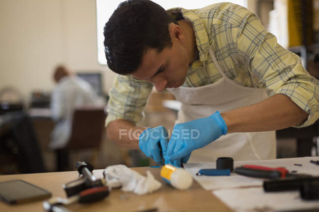 Attentive man cleaning bicycle parts on counter in workshop — Stock Photo