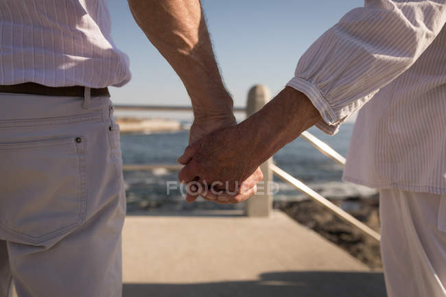 Mid section of senior couple standing at promenade — Stock Photo