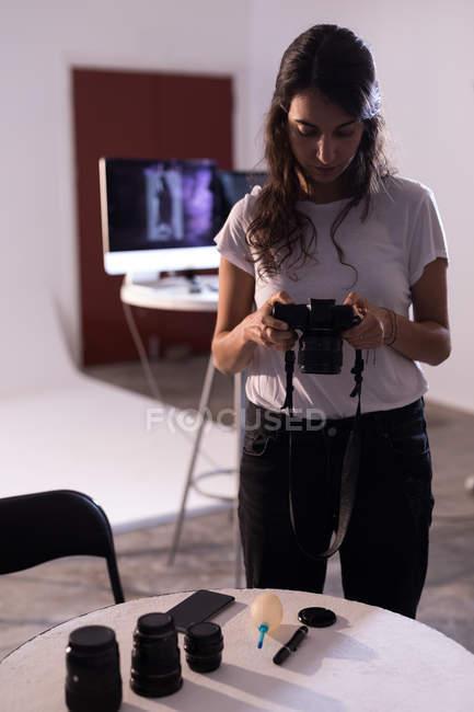 Modello femminile che rivede le foto sulla fotocamera digitale in studio fotografico — Foto stock
