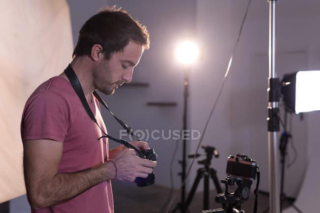 Чоловічий фотограф рецензування фотографії на цифрові камери в фотостудії — стокове фото