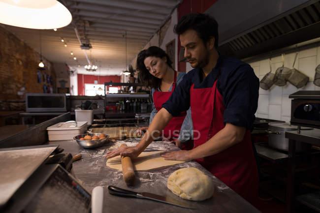 Panettiere maschio che rotola un impasto di farina mentre fa la pasta in un panificio — Foto stock