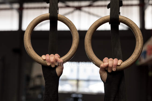Fit woman exercising on gymnastic rings in fitness gym — Stock Photo