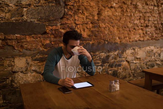 Mann trinkt Kaffee, während er eine digitale Registerkarte benutzt — Stockfoto