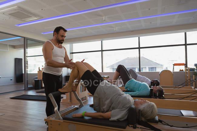 Trainer unterrichten Gruppe von Frauen in Führungspositionen bei der Ausübung von Yoga im Yoga-Zentrum — Stockfoto