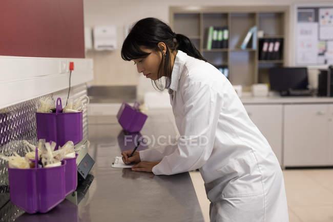 Technicien de laboratoire notant le poids des sacs de sang dans la banque de sang — Photo de stock