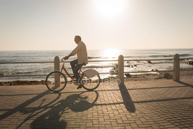 Senior man riding bicycle at promenade on a sunny day — Stock Photo