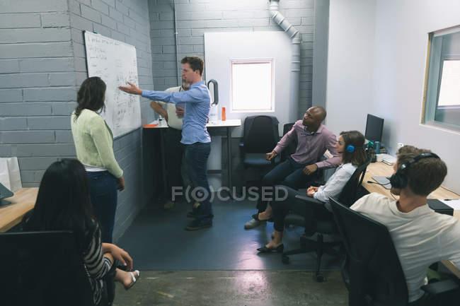 Gens d'affaires discuter au tableau blanc au bureau — Photo de stock